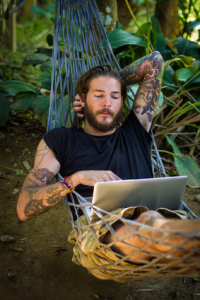 Man lying in hammock with laptop