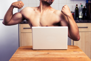 muscular man in front of computer